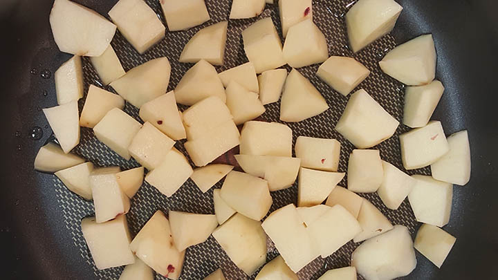 cubed potato added to cooking pan